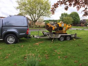Arriving to Remove a Tree Stump. tree stump removal machine being towed