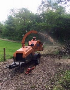 orange grinder firing out tree cuttings