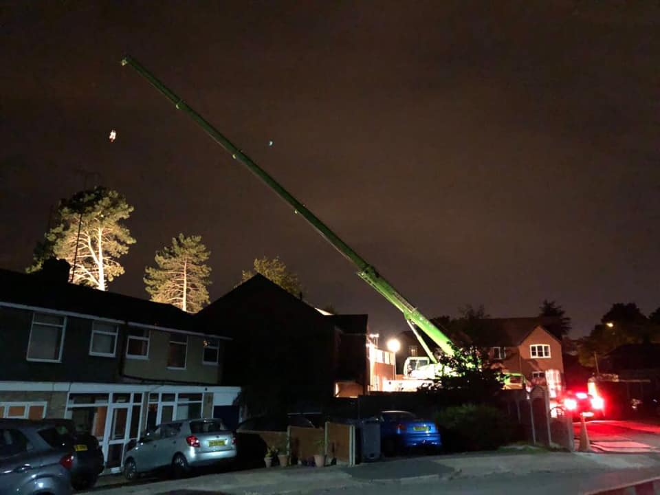 night removal. green crane working on an evening
